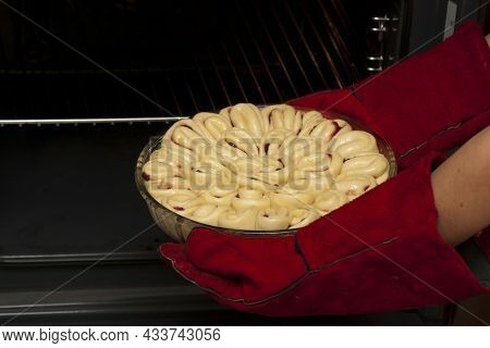 The Pie With Fruit Filling Is Planted In The Oven. A Baker Wearing Heat-resistant Gloves Puts A Pie