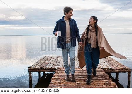 Positive Multiethnic Couple With Cup And Blanket Walking On Pier