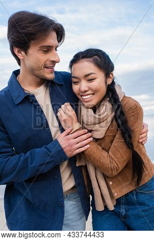 Positive Multiethnic Couple Hugging Outdoors During Weekend