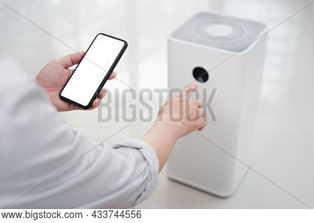 Close Up Hand A Man Holding Smartphone With White Screen Display And Online Connect To Air Purifier