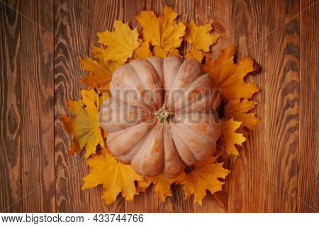 Autumn Composition Of Pumpkin And Yellow Leaves On A Brown Wooden Background. The Concept Of Thanksg