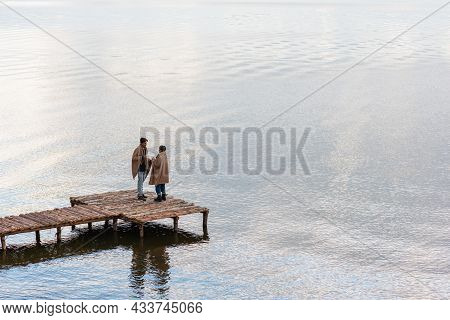 Multiethnic Couple In Blankets Holding Cups While Talking On Pier