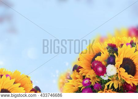 Sunflowers And Aster Fresh Flowers Border On Defocused Blue Fall Sky Background