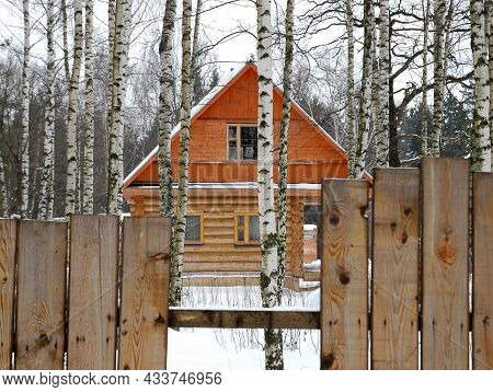 A Rustic Wooden House Behind A Fence. A Gap In The Fence. Rural Landscape. Village, Village.