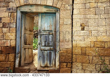 Antique Door With Old Blue Paint, Shabby From Time To Time. Stone Wall With A Doorway And A Door In