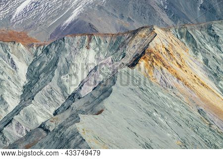 Multicolor Autumn Landscape With Snow-covered Mountain And Gray Rockies With Orange And Lilac Tint.