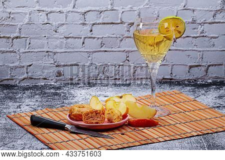 A Glass Of Wine With Lemon, A Saucer With Eclairs And Apple Slices On The Kitchen Table. Photo Of Fo