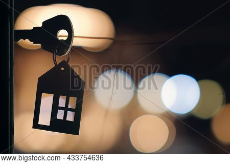 The Key With Keyring In The Door Keyhole With Blurred Night Lights Background, Selective Focus
