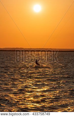 Acrobatic jump of professional kite surfer on the sea wave, athlete showing sport trick jumping with kite and board in air. Extreme water sport and summer vacations concept