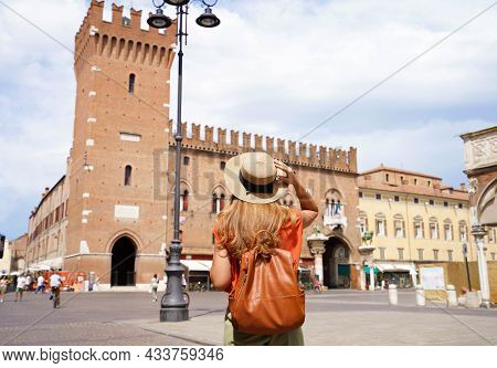 Cultural Tourism In Italy. Rear View Of Female Backpacker Visiting Old Medieval Town Of Ferrara, Ita