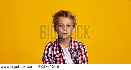 Serious Seriously Calm Cute Caucasian Teenage Boy Looking At Camera, Isolated On Yellow Background