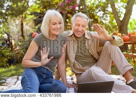 Happy Married Senior Couple Using Laptop Computer And Video Calling Family, Sitting On Picnic Blanke