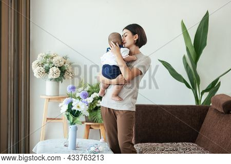 Asian Mother Holding Love Newborn, Mom Holding Newborn Living At Home. Mother's Day Concept.