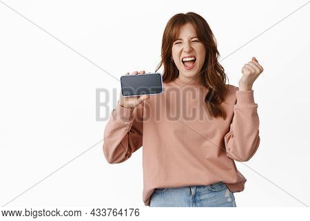 Excited Redhead Woman Showing Horizontal Screen Mobile Phone, Celebrating And Screaming From Joy, Sh