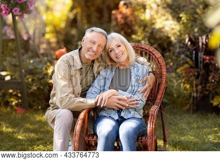 Loving Elderly Spouses Resting In Countryside, Woman Sitting In Wicker Chair, Man Embracing Wife, Co