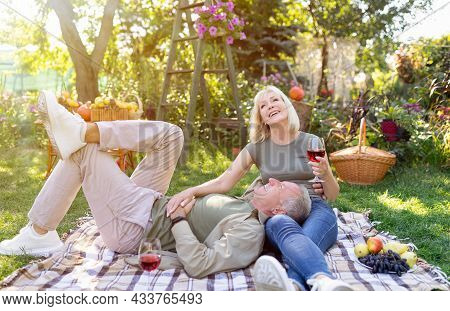 Romantic Senior Spouses Enjoying Picnic Together, Resting On Blanket In Garden And Drinking Red Wine