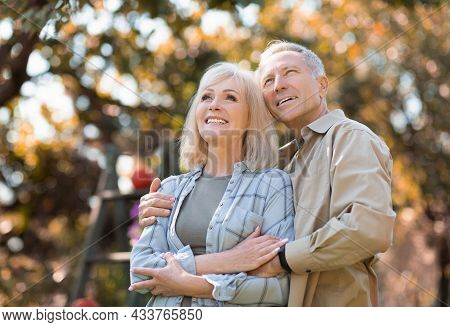Happy Elderly Spouses Enjoying Warm Autumn Days And Peaceful Nature, Man Embracing Wife, Free Space