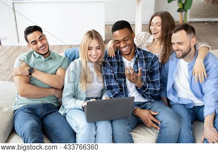 Cheerful Diverse Friends Using Laptop Pc, Sitting On Sofa In Living Room, Having Video Call, Chattin
