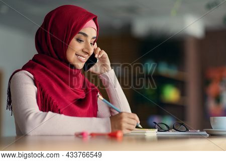 Happy Middle-eastern Woman In Hijab Having Phone Conversation