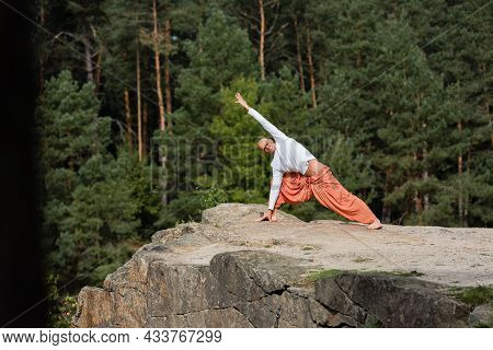 Buddhist In Sweatshirt And Harem Pants Practicing Yoga In Side Lunge Pose On Rocky Cliff