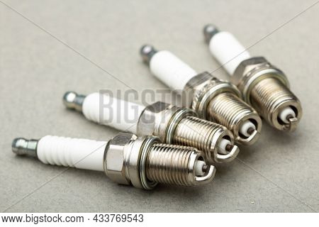 New car spark plugs on gray background