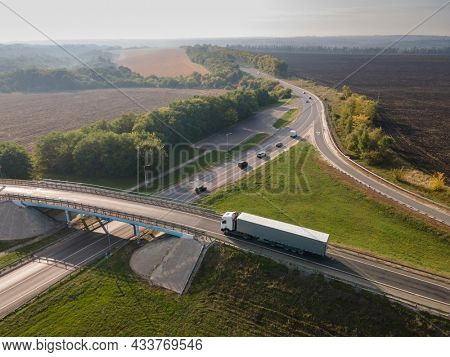 Truck with Cargo Semi Trailer Moving on Road in Direction. Highway intersection junction. Aerial Top View