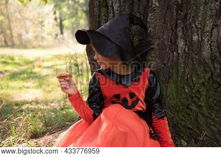 Portrait Of A Witch. A Girl Dressed As A Witch Holds An Amanita In Her Hand. A Mushroom For A Witchs