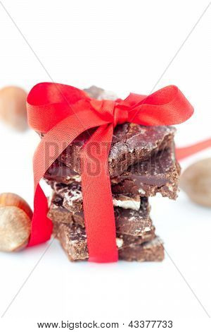 Background Of Stack Of Chocolate With Red Ribbon And Nuts