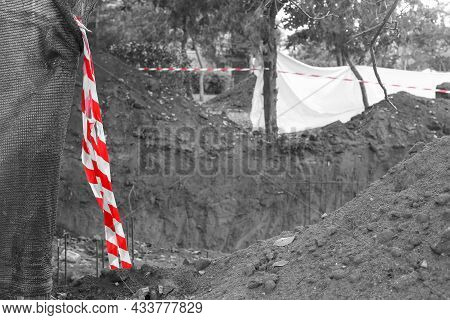 Fencing Tape Red And White. The Tape Protects People From Construction Site. The Foundation Pit. Red