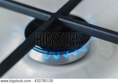 Close-up Of A Black Burner Of A White Enameled Gas Stove With A Blue Fire. Cast-iron Grates For Kitc