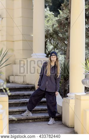 A Girl In Wide Trousers And A Shirt Stands Near The Steps Against The Background Of Columns. Hiphop