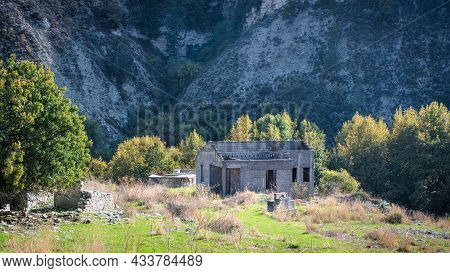 Ruins Of Stone House Without Roof And Overgrown Garden At The Foot Of A Mountain. Abandoned Village