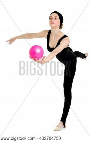 Flexible Girl Gymnast Balancing On One Leg With Ball. Beautiful Teenage Girl Doing Gymnastic Exercis