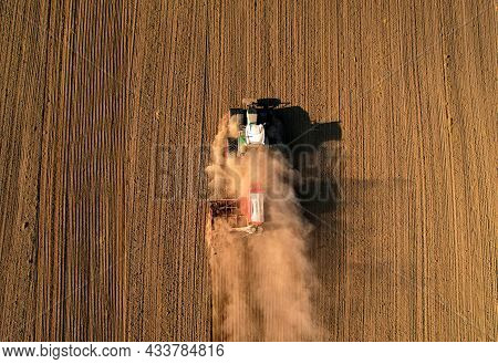 Agricultural Tractor On Sowing Seeds At Field. Farming And Seeding Concept. Seed Sowing In Soil In F