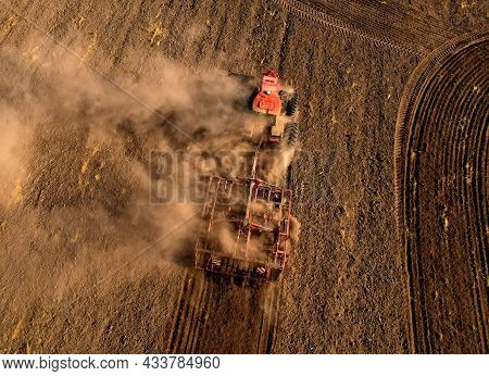 Soil Tillage In Farmers Country. Red Tractor On Cultivating Field Work. Agricultural Tractor On Cult