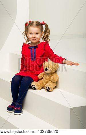 A Little Girl Sits On A White Staircase With A Teddy Bear. Adorable Cute Baby With Ponytails, Dresse