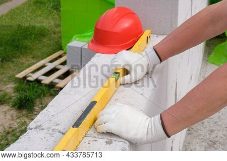 Builders Hands In A Glove And A Building Level To Check The Wall Outdoors.