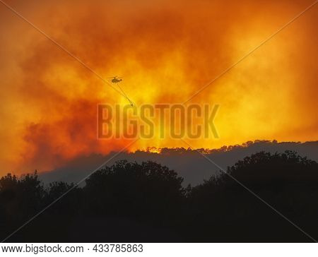 Helicopter With Water Bucket Fighting Forest Wildfire At Night, Dramatic Landscape With Red Sky And