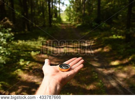 Compass In Hand At Road In The Forest. Tourist Compass For Orientation On The Terrain. Magnetic Decl