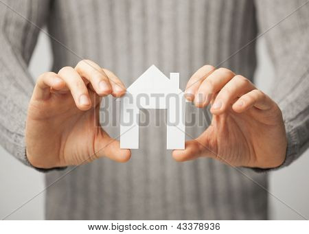 bright picture of man holding paper house