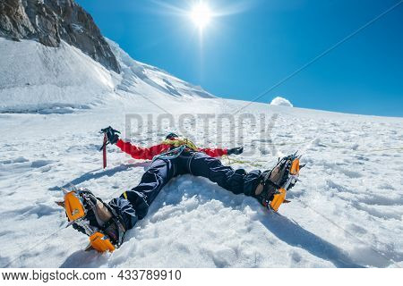 Tired Exhausted Climber Lying Under Mont Blanc Du Tacul Mountain. Wide Opened Legs In Boots With Cra