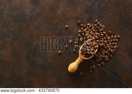 Coffee Beans In A Wooden Scoop Isolated On A Dark Background. Roasted Coffee Beans Isolated. A Woode