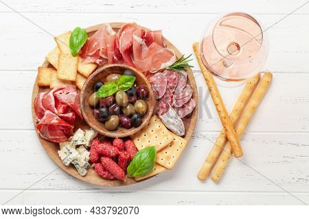 Antipasto board with prosciutto, salami, crackers, cheese, nuts, olives and rose wine. Top view flat lay