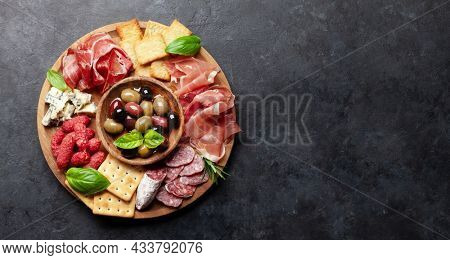 Antipasto board with prosciutto, salami, crackers, cheese and olives. Top view flat lay with copy space