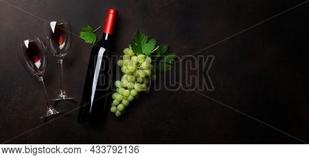 Two red wine glasses, wine bottle and grape. Top view flat lay with space for your text