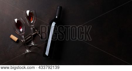 Wine glasses, red wine bottle and vintage corkscrew. Top view flat lay with space for your text