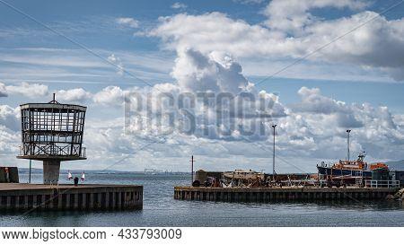 Entrance To Carrickfergus Marina Or Port Between Two Breakwaters. Boat Maintenance In Drydock, North