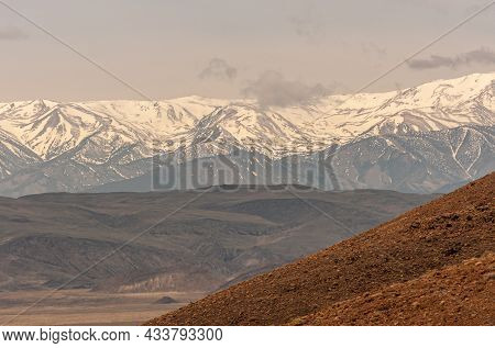 High Desert, Nevada, Usa - May 17, 2011: Wall Of Snow Covered Mountain Range Under Gray Sky. Brown S