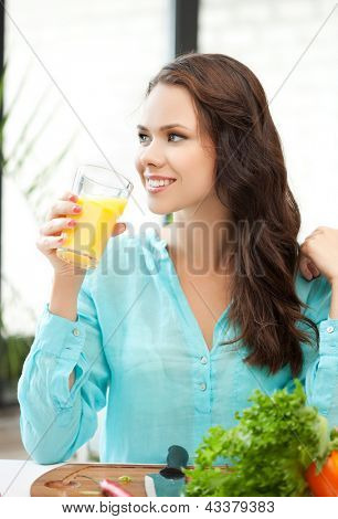 young woman holding glass of orange juice