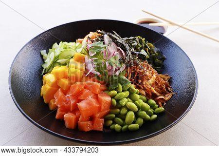 Healthy Poke Bowl With Edamame, Salmon, Wakame Seaweed, Mango, Radish, Cucumber, Onion And Rice Serv